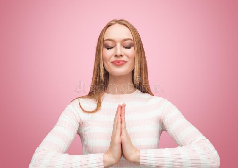 Härlig flicka som lyckligt mediterar på rosa färger arkivfoton