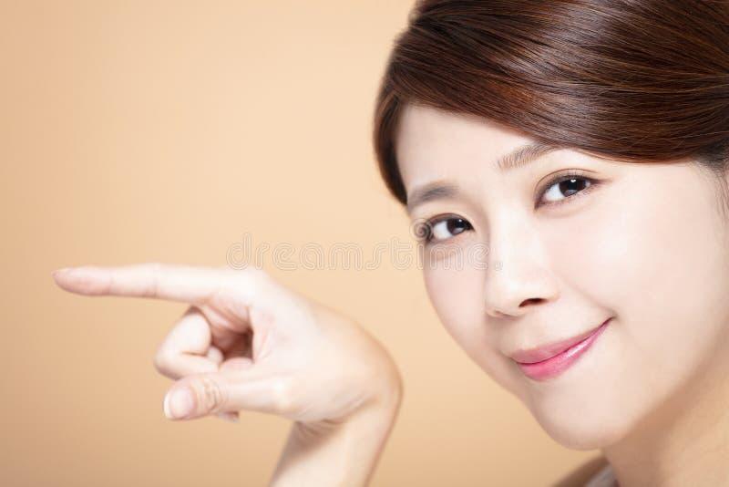 Härlig flicka som pekar till sidan royaltyfri foto