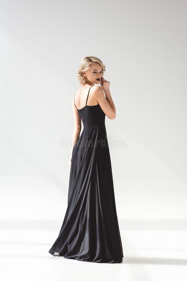 härlig flicka som poserar i elegant svart klänning, royaltyfria bilder