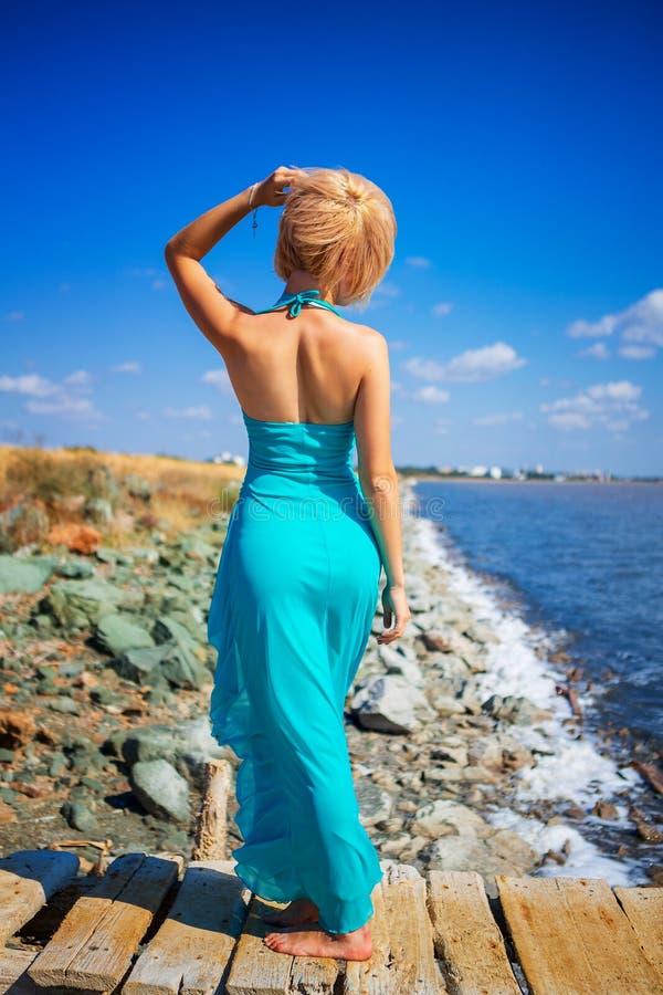 Härlig flicka som poserar på pir på en solig sommardag arkivfoton