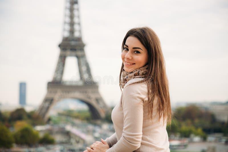 Härlig flicka som poserar till fotografen mot bakgrunden av Eiffeltorn Höstphotosession soligt väder arkivfoto