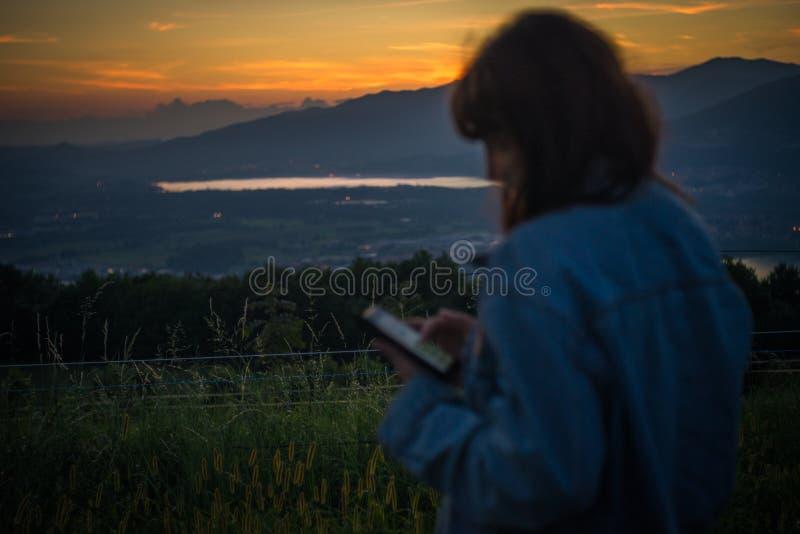Härlig flicka som pratar på socialt massmedia med hans smartphone på solnedgången över sjön arkivfoton