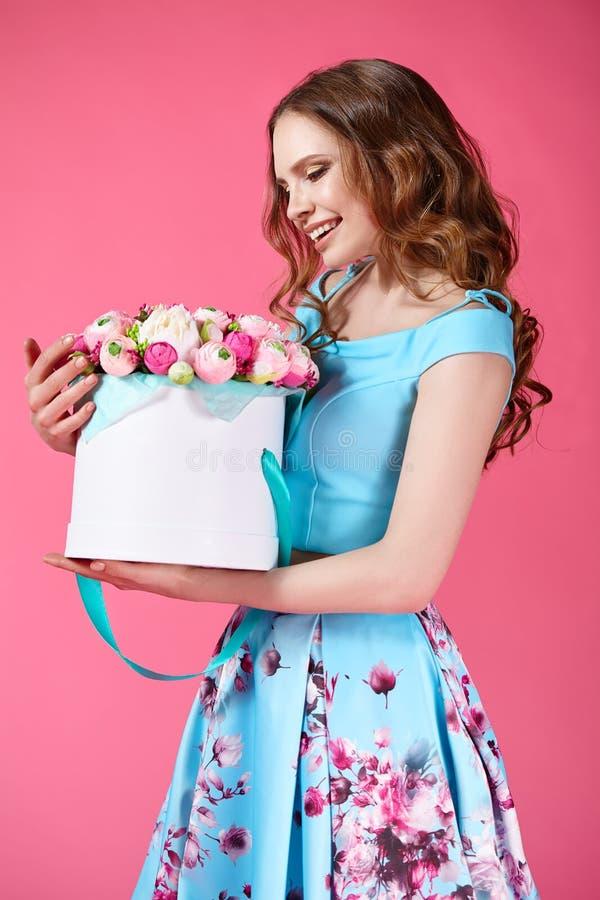 Härlig flicka som rymmer den stora buketten av pappers- blommor i ask royaltyfri bild