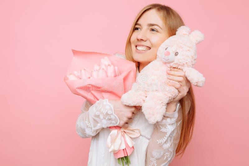 Härlig flicka som rymmer en nallehare och en bukett av tulpan i hennes händer, på en rosa bakgrund valentin för dag s arkivfoto