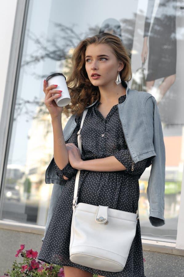 Härlig flicka som rymmer en pappers- kopp med en drink arkivbild