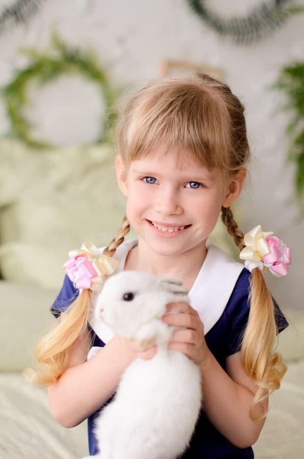 härlig flicka som rymmer en vit kanin arkivbild
