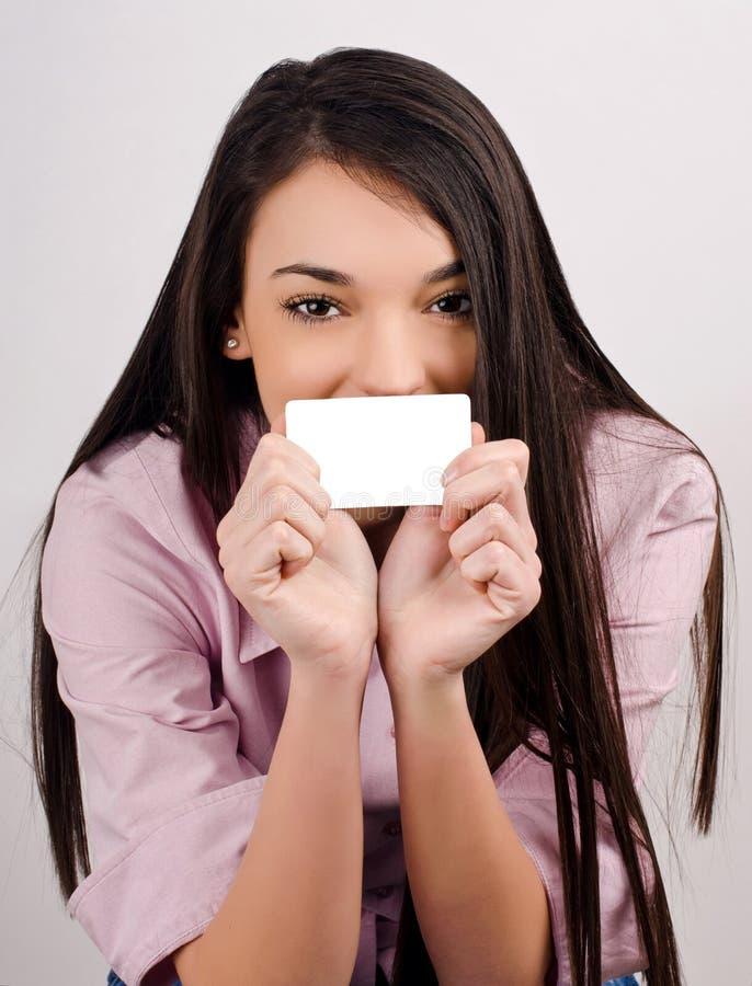 Härlig flicka som rymmer ett besökkort. royaltyfria foton