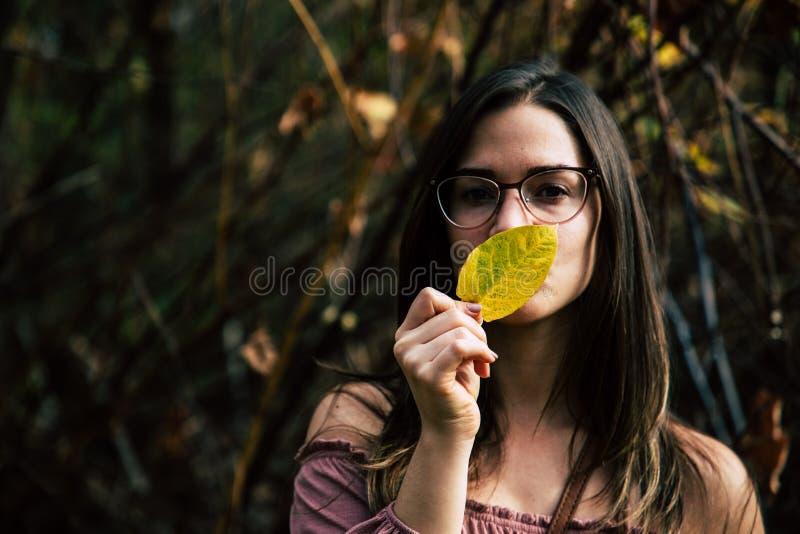 Härlig flicka som rymmer ett gult blad som täcker hennes mun arkivbild