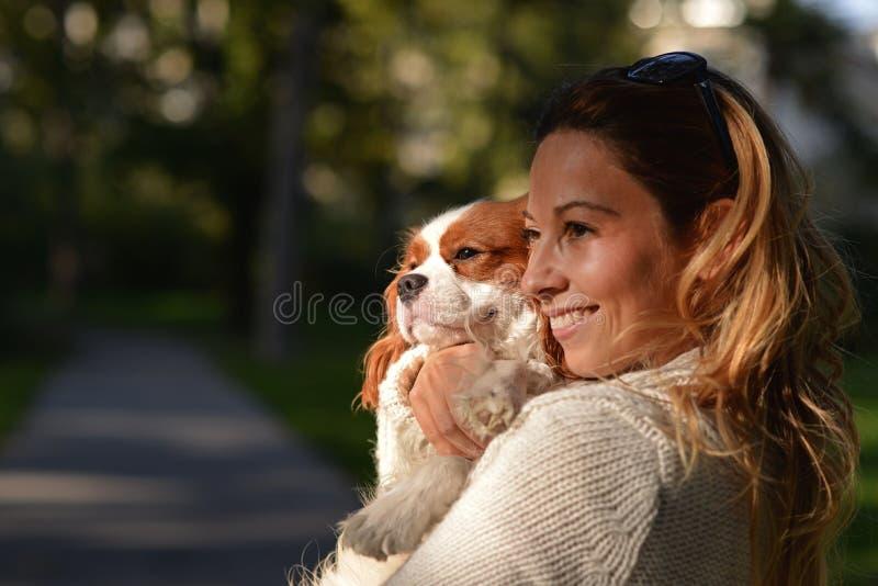 Härlig flicka som rymmer hennes stolta konung Charles Spaniel för hund arkivbild
