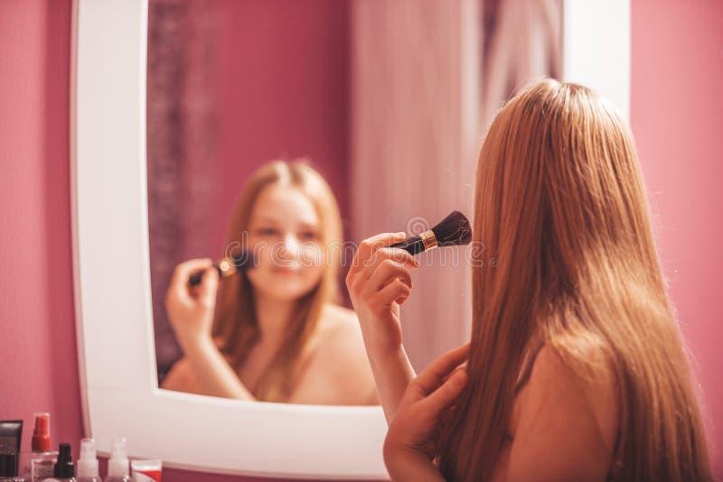 Härlig flicka som ser i spegeln och applicerar makeup royaltyfri fotografi