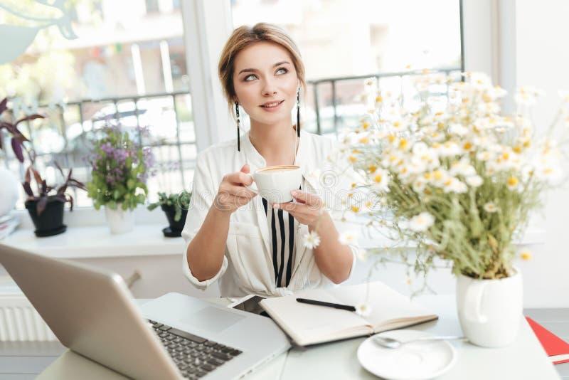 Härlig flicka som sitter i coffee shop med koppen kaffe i händer och dreamily åt sidan ser arkivbild