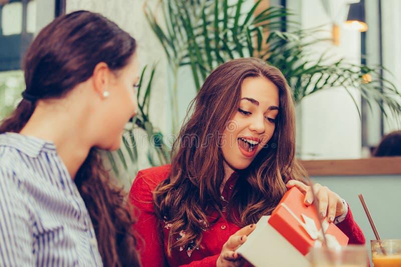 Härlig flicka som sitter i kafé med hennes vän och mottar en gåva arkivfoton