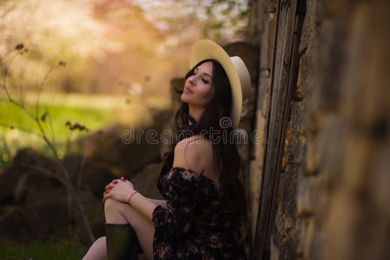 Härlig flicka som sitter mot ett lantligt landskap fotografering för bildbyråer