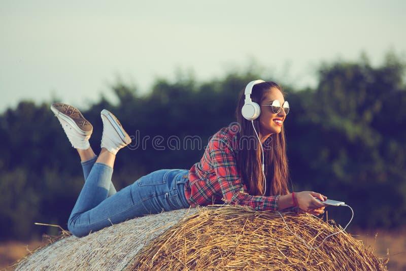 Härlig flicka som sitter på en höstack och att lyssna till musik som tycker om solnedgång arkivfoton