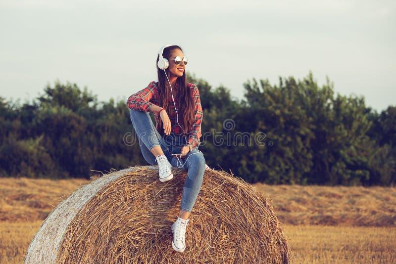 Härlig flicka som sitter på en höstack och att lyssna till musik som tycker om solnedgång arkivfoto