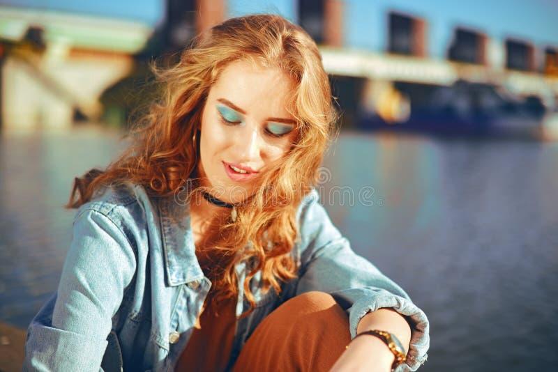 Härlig flicka som sitter på pir nära floden Blond modell för Hipster med ursnyggt för hår cerly Flickan i grov bomullstvillomsl royaltyfri foto