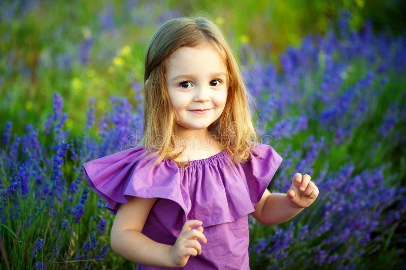 Härlig flicka som spelar i blommande lavendelblommafält Barnlek i vårblommor arkivfoto