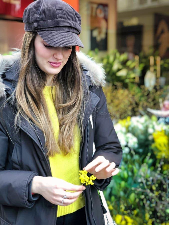 Härlig flicka som spelar med den lilla filialen av mimosan fotografering för bildbyråer