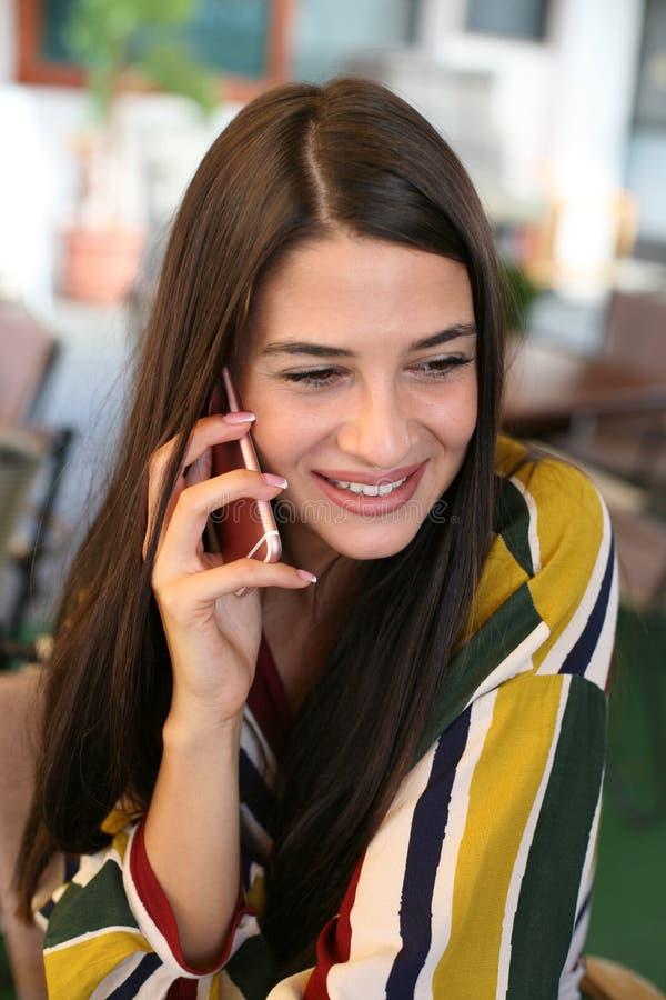 Härlig flicka som talar på den smarta telefonen arkivbild