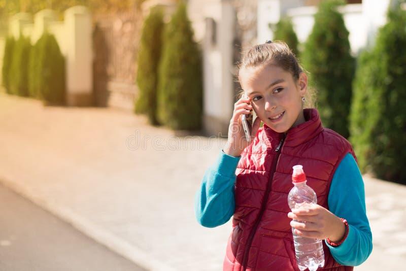 Härlig flicka som talar på en smartphone i röd väst arkivfoto