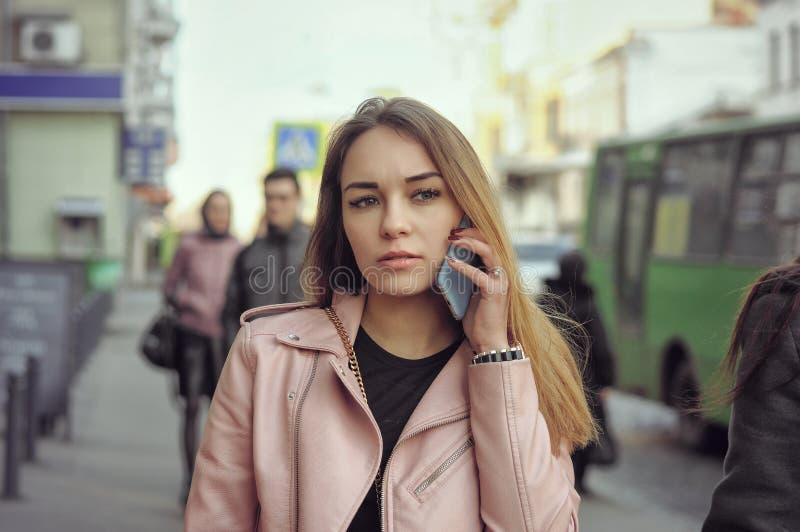 Härlig flicka som talar på telefonen, medan gå på det sidewal royaltyfria foton