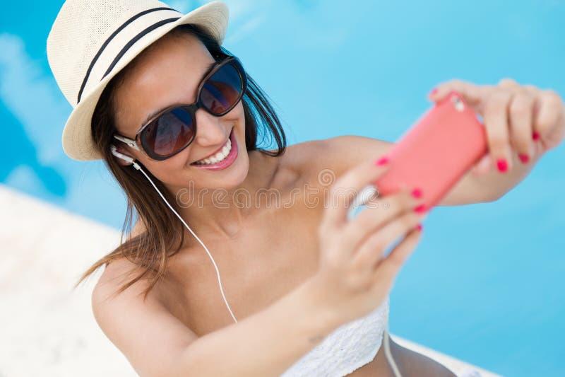 Härlig flicka som tar en selfie på simbassängen royaltyfri bild