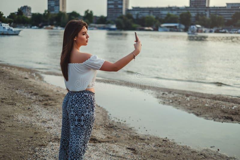 Härlig flicka som tar selfie på stranden royaltyfri fotografi