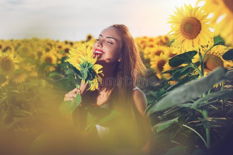 Härlig flicka som tycker om naturen på fältet av solrosor på solnedgången fotografering för bildbyråer