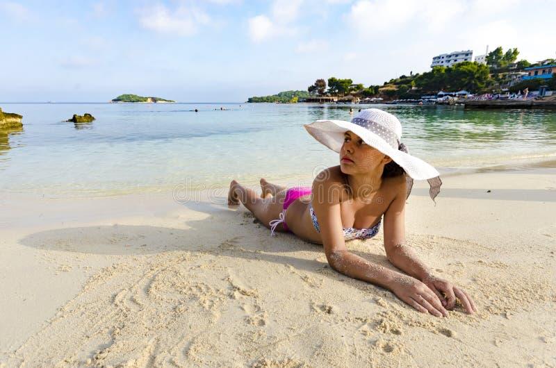 Härlig flicka som tycker om på den vita sanden på det Ionian havet royaltyfria foton