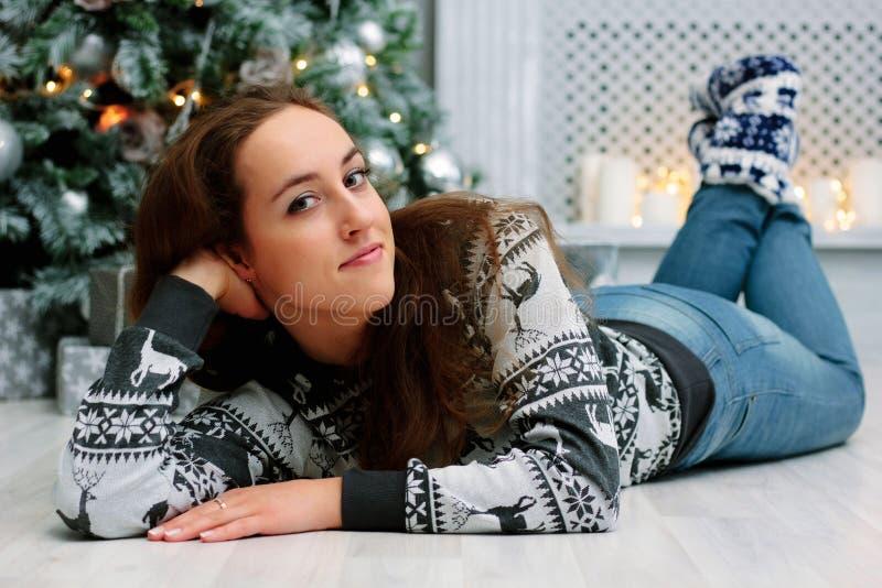 Härlig flicka under jul som lägger ner på golv nära julträd arkivfoton