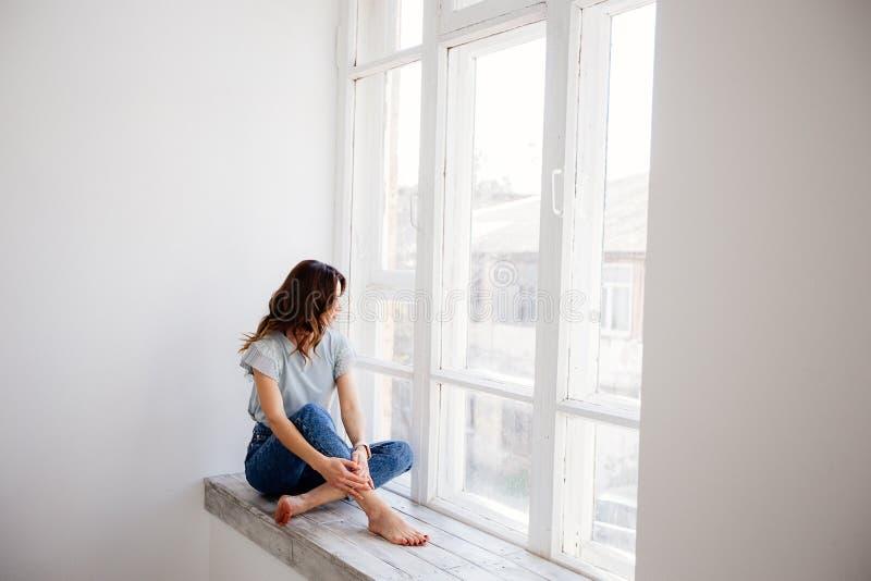 Härlig flicka vid fönstret arkivbilder