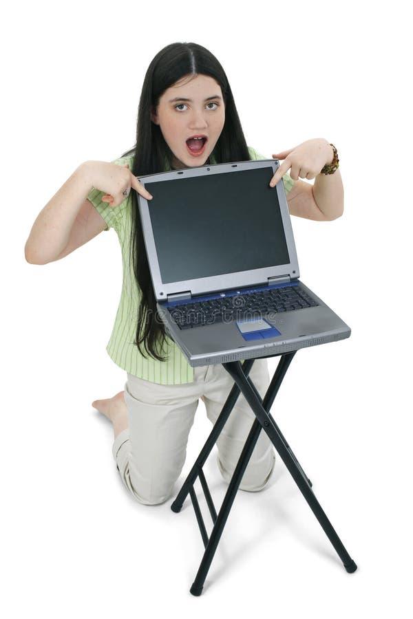 härlig flickabärbar dator som pekar skärmen till tween fotografering för bildbyråer