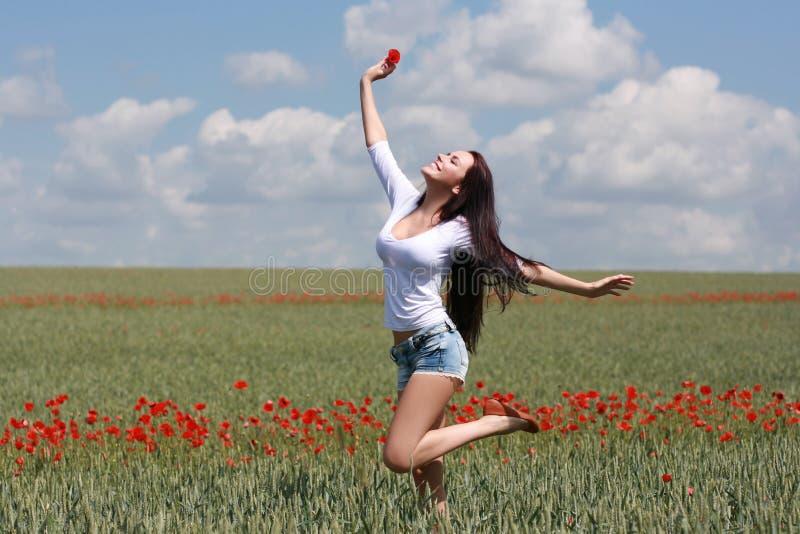 Härlig flickabanhoppning i ett fält med vallmo fotografering för bildbyråer