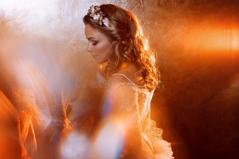 Härlig flickabrud i den lyxiga bröllopsklänningen, stående i guld- signaler, effekter av ilsken blick royaltyfria bilder