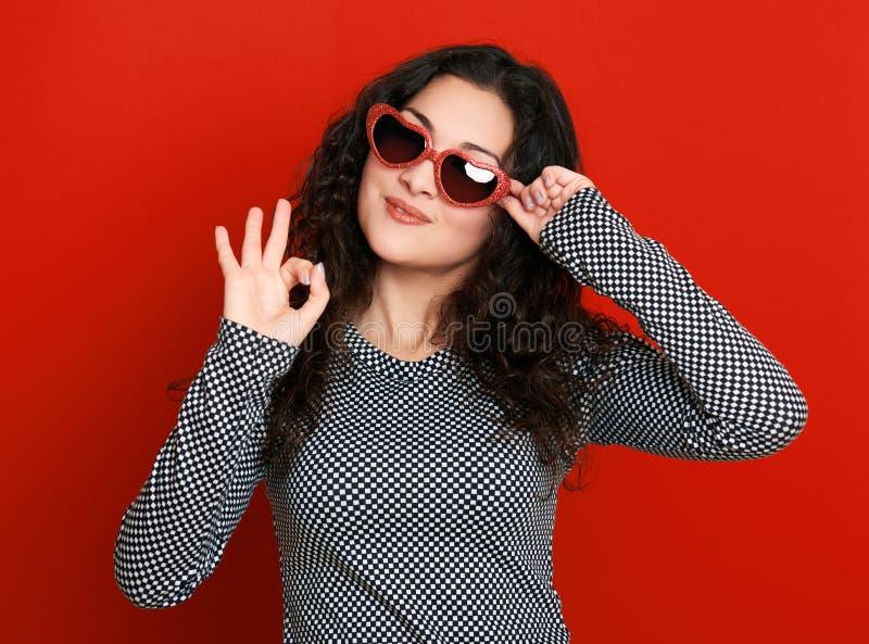 Härlig flickaglamourstående på rött i hjärtaformsolglasögon, långt lockigt hår royaltyfria foton