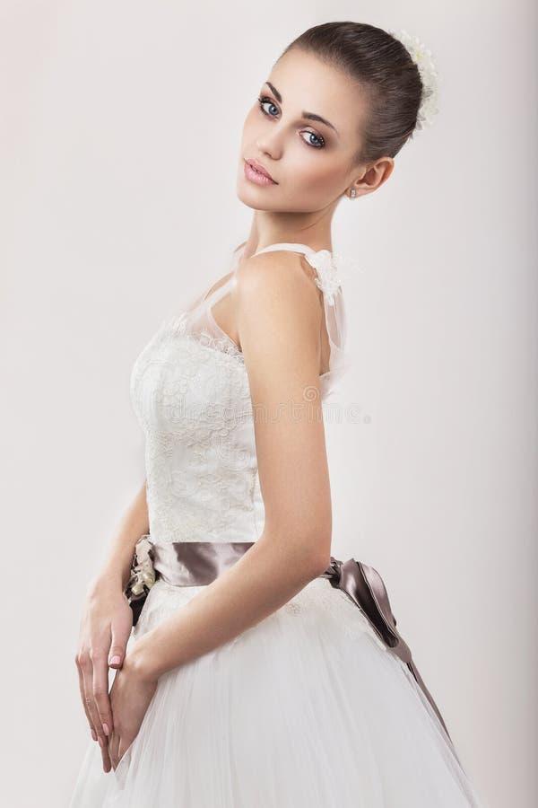 Härlig flickamodell i form av en brud i hennes bröllopsklänning Härlig le flicka arkivbild