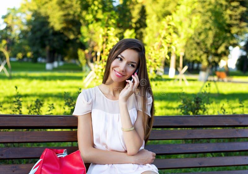 Härlig flickasammanträdebänk, brunett i en rosa klänning, modelivsstil som talar till telefonen royaltyfria foton