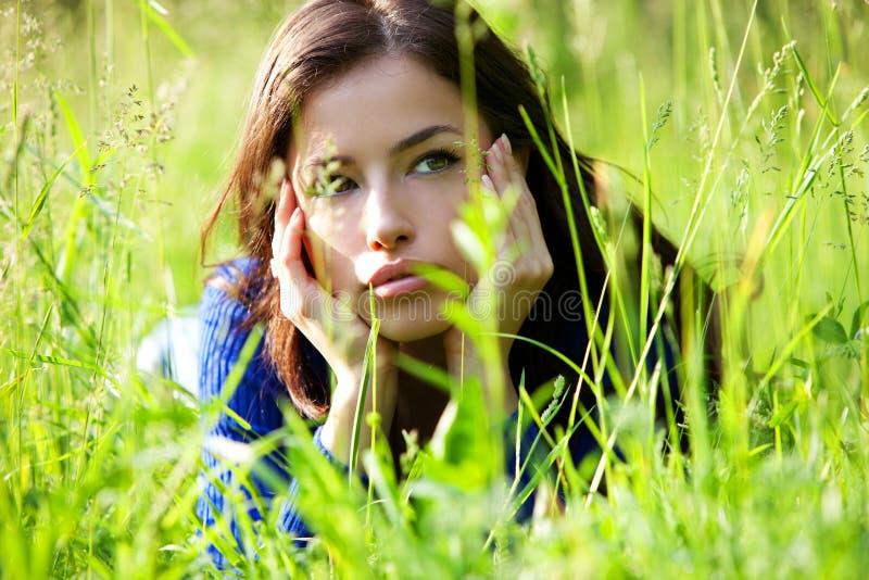 Härlig flickastående i gräs royaltyfri foto