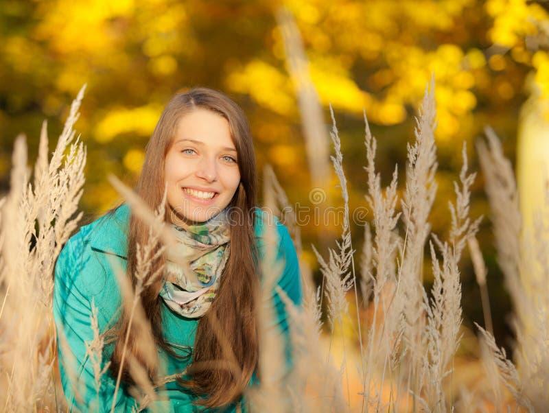 Härlig flickastående i höstgräs royaltyfria foton