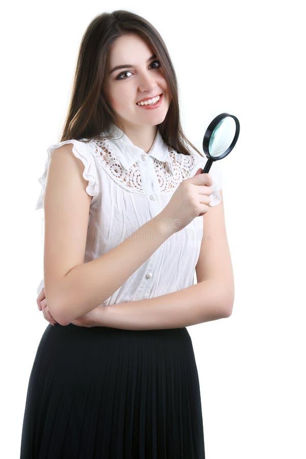 Härlig flickastående som ser till och med förstoringsapparaten isolerat fotografering för bildbyråer