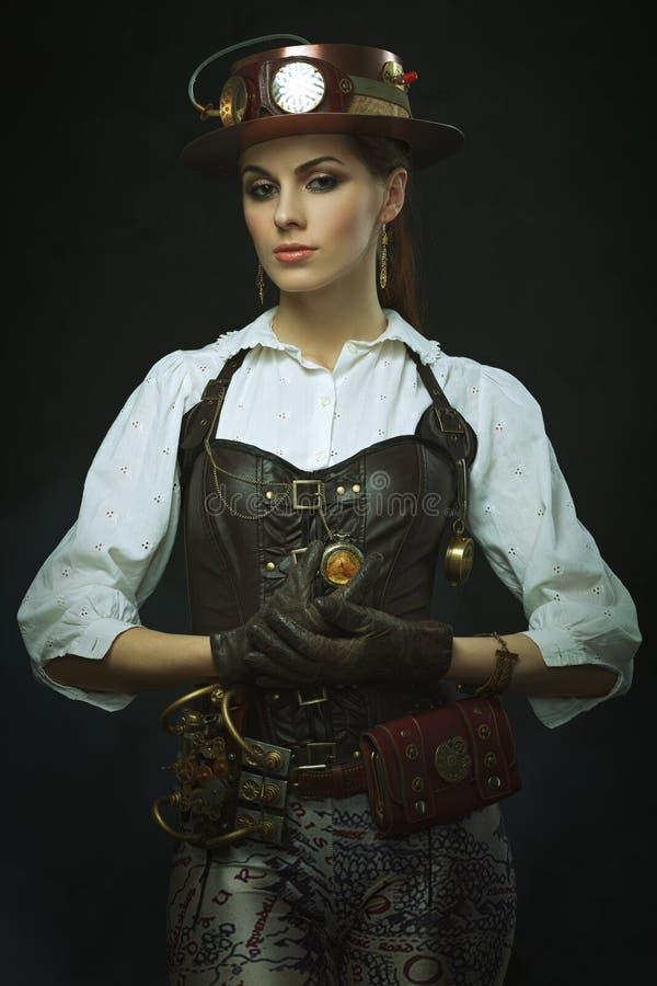 Härlig flickasteampunk Posera med klockan arkivfoto