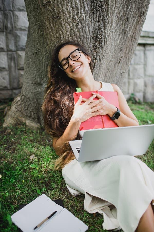 Härlig flickastudent som lär hennes kurser som sitter på gräs arkivbilder