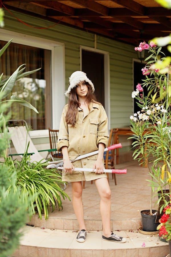 Härlig flickaträdgårdsmästare med långt hår i funktionsduglig kläder fotografering för bildbyråer