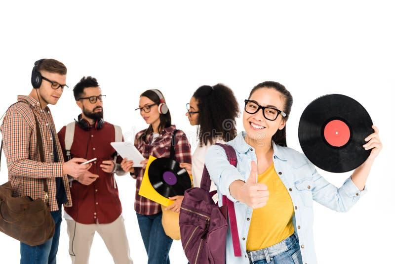 härlig flickavisningtumme upp, medan rymma vinylrekordet nära den milticultural grupp människor isolerat royaltyfri fotografi