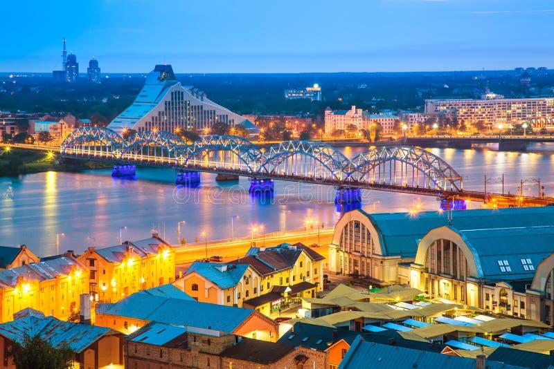 Härlig flyg- panorama av Riga Resa med tåg bron över Daugavafloden och nationellt arkiv under fantastisk solnedgång Sikt av illum royaltyfria bilder