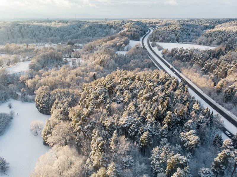 Härlig flyg- sikt av dolda pinjeskogar för snö och en vägspolning bland träd Rimfrostis och hoarfrost som täcker träd Vinter royaltyfria foton