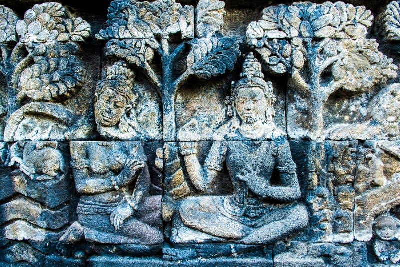 Härlig forntida väggkonstlättnad med Buddha, buddistisk tempel komplexa Borobudur, Yogyakarta, Jawa, Indonesien arkivbild
