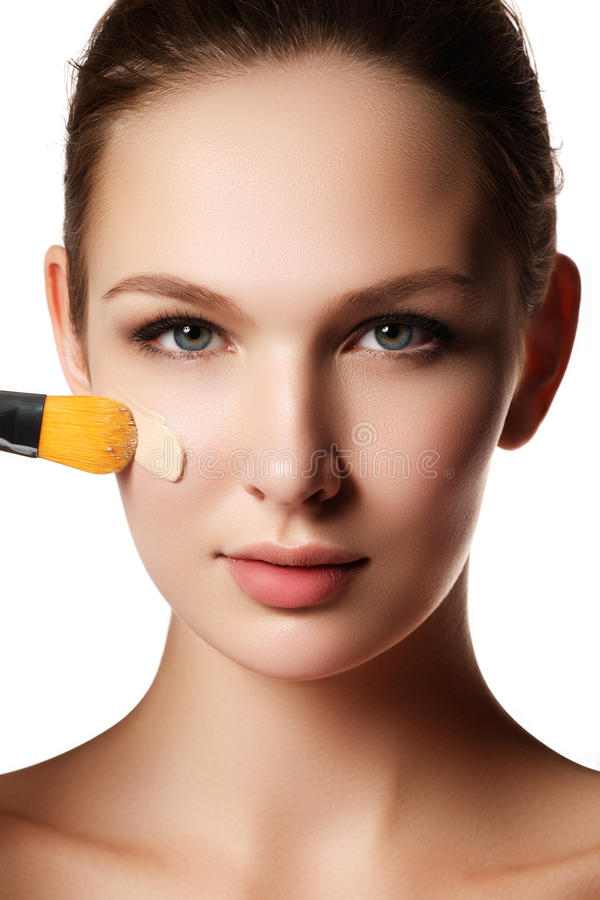 Härlig framsida av den unga kvinnan med det kosmetiska fundamentet på en hud royaltyfri foto