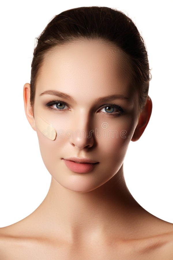 Härlig framsida av den unga kvinnan med det kosmetiska fundamentet på en hud fotografering för bildbyråer