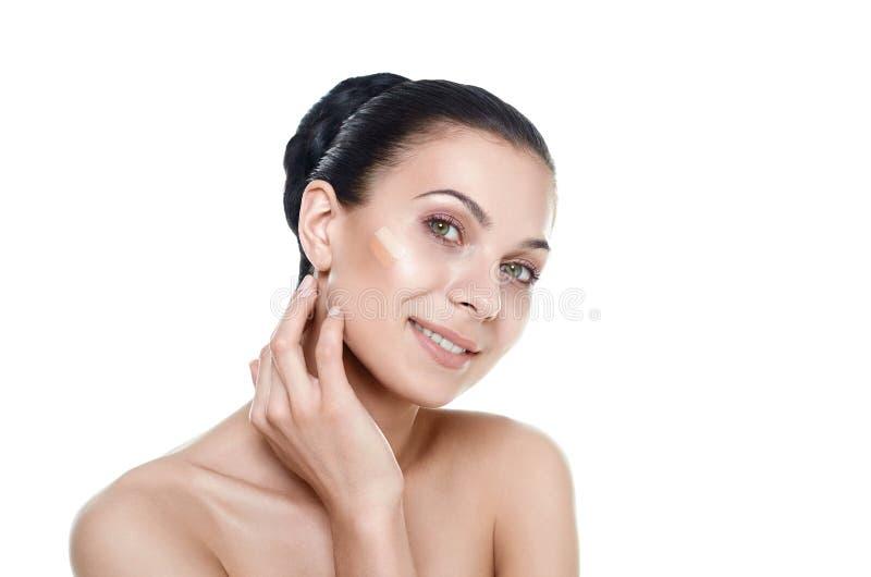 Härlig framsida av den unga kvinnan med det kosmetiska fundamentet på en hud arkivbild